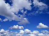 Sunlit Fluffy White Clouds in a Blue Sky Photographic Print by Jason Edwards