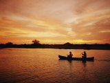 A Couple Rowing a Canoe is Silhouetted against a Gorgeous Sunset Photographic Print by Barry Tessman