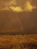 Storm Clouds and a Rainbow Appear over the Prairie Landscape Photographic Print by Paul Damien