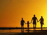 A Family Holding Hands is Silhouetted against the Setting Sun Fotoprint van Rich Reid