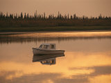 An Anchored Boat Floats on the Mackenzie River at Sunset Photographic Print by Raymond Gehman