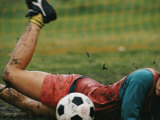 A Soccer Player Lands in the Mud in an Attempt to Field the Ball Photographic Print by Dugald Bremner