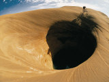 A Mountain Biker Cycles Around a Spectacular Crater in the Desert Photographic Print by Dugald Bremner