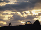 A Mountain Biker Cycles Toward Tents at a Campsite Photographic Print by Dugald Bremner