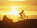 A Woman Rides Her Bike in the Sunset with Rock Cliffs in the Background Fotoprint van Dugald Bremner