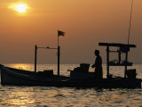 A Silhouetted Boat Fishing for Soft Crabs Photographic Print by Robert Madden