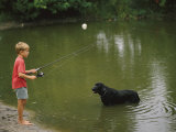 Boy Fishing in a Pond with a Black Labrador Retriever Standing in the Water Photographic Print by Brian Gordon Green
