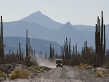 A Truck Travels Through a Landscape of Mountains and Saguaro Cacti Photographic Print by Annie Griffiths Belt