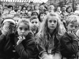 Audience of Children Sitting Very Still, with Rapt Expressions, Watching Puppet Show at Tuileries Premium Photographic Print by Alfred Eisenstaedt