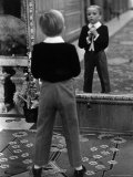 English Boy Using Reflection in Mirror in Foyer of Grand Hotel to Fix His Tie Photographic Print by Alfred Eisenstaedt