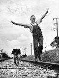 Larry Jim Holm with Dunk, His Spaniel Collie Mix, Walking Rail of Railroad Tracks in Rural Area Photographie par Myron Davis