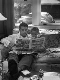 Father Sitting on Couch with Pigtailed Daughter Reading to Her the Sunday Comic Pages Lámina fotográfica de primera calidad por Nina Leen