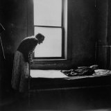 Daylight Cast from Window Reveals Old Woman Bent over the Foot of Bed Gazing Tenderly on Cloth Doll Photographic Print by Wallace Kirkland