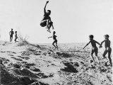 Bushman Children Playing Games on Sand Dunes Reproduction photographique par Nat Farbman