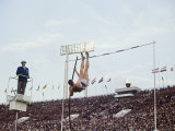 Athlete Clearing the Pole Vault at Summer Olympics Reproduction photographique par John Dominis