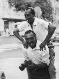 Italian Man Leaping Onto a Friend's Back in Casual Greeting While Crossing a Piazza Photographic Print by Paul Schutzer