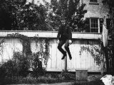 Man in a Suit and Bowler Hat Jumping in the Air in a Backyard in Brooklyn, Ny Photographic Print by Wallace G. Levison