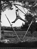 Kenneth Merriman Swinging on Tree Limb After Kicking Away Stilts Premium Photographic Print by Robert W. Kelley