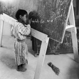 Child Writing a Sentence on the Blackboard at School Photographic Print by John Phillips