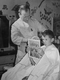 12 Year Old Boy Sitting in Barber Chair Having His Hair Cut and Reading Comics Premium Photographic Print by Alfred Eisenstaedt