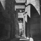 Man Walking Past Huge Carved Columns in Temple of Amon at Karnak in Thebes Photographic Print by Eliot Elisofon