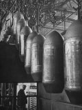 Line of 500 lbs Bombs Jiggling Along on Overhead Conveyor Hooks Abover Worker Premium Photographic Print by Andreas Feininger