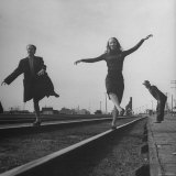 Two Young Ballet Russe Dancers Balancing on the Railroad Tracks in the Station While on Tour Photographic Print by Myron Davis