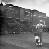 Young Boy and His Dog Standing at the Crossing as a Train Rides Through Photographic Print by Myron Davis