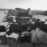 Airplanes Sitting on Airstrip at Airfield and Supplies Sitting in Trucks Photographic Print by Jack Birns