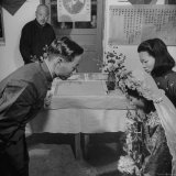 Bride and Groom Exchanging Rings During Wedding at Hwa Ching Hot Springs Photographic Print by Mark Kauffman
