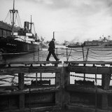 Man Walking Across Gateway Leading from Bramley Moore Dock Into Sanden Half Tide Dock Photographic Print by Nat Farbman