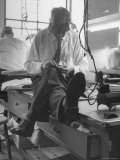 Custom Tailor Ernest Preedik Sitting on Table and Working in Factory Premium Photographic Print by Ralph Morse