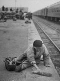 Aged Refugee Fighting Hunger, Sweeps Up Spilled Rice on the Railroad Station Platform Photographic Print by Jack Birns