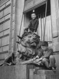 Children Playing on the Sculpted Lion at the Entrance of a Bank Premium Photographic Print by George Lacks