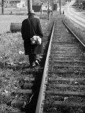 Elderly Hobo, with Bundle Strapped to His Back, Walking Along Train Tracks Photographic Print by Carl Mydans