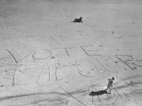 "Girl Standing by the Words ""Vote Labour"" Written in the Sand Photographic Print by Cornell Capa"