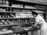 Good of Worker in Bakery Standing in Front of Shelves of Various Kinds of Breads and Rolls Premium Photographic Print by Alfred Eisenstaedt