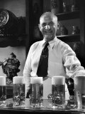 Bartender Smiling as He Serves Large Glasses of Beer Photographic Print by Frank Scherschel