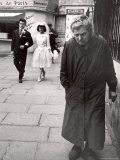 Elderly Woman Walking Along Street While Bride and Groom Walk Behind Photographic Print by Alfred Eisenstaedt