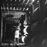 Employee in Warehouse of Jack Daniels Distillery Checking For Leaks in the Barrels Photographic Print by Ed Clark