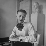 Model Wearing Flower Accessories While Peering Into the Distance Photographic Print by Nina Leen
