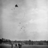 Children Playing with Kite That Releases Toys While in the Air Photographic Print by Bernard Hoffman