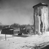 Landscape View of Frozen Wooden Water Tower and Unattractive Brick Buildings Photographic Print by Walker Evans