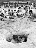 Couple Cuddling While Sitting in a Hole as Others Enjoy the Beach on the 4th of July Reproduction photographique sur papier de qualité par Ralph Crane