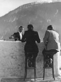 British Couple on High Stools at Ice Bar Outdoors at Grand Hotel as Waiter Pours Them Drinks Fotoprint van Alfred Eisenstaedt