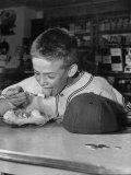 Boy Wearing Baseball Uniform Eating Banana Split at Soda Fountain Counter Premium Photographic Print by Joe Scherschel