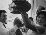 Bride and Groom Breaking Bread During Wedding Premium Photographic Print by Paul Schutzer