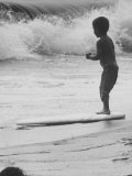 Little Boy Standing on a Surf Board Staring at the Water Fotografie-Druck von Allan Grant