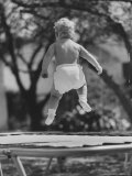 Baby Jumping on a Trampoline Premium Photographic Print by Ralph Crane