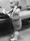 Baby Playing with a Telephone Photographic Print by Yale Joel